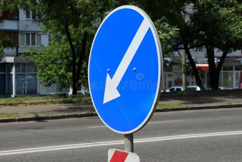 blått vägmärke med den vita pilen på stadsvägen arkivfoto