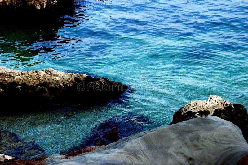 Blått vatten av Adriatiskt havet som tvättar några stenar royaltyfria foton