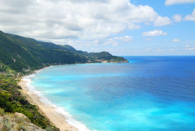 Blått vatten för kust- hav med stranden och den branta kullen royaltyfria bilder
