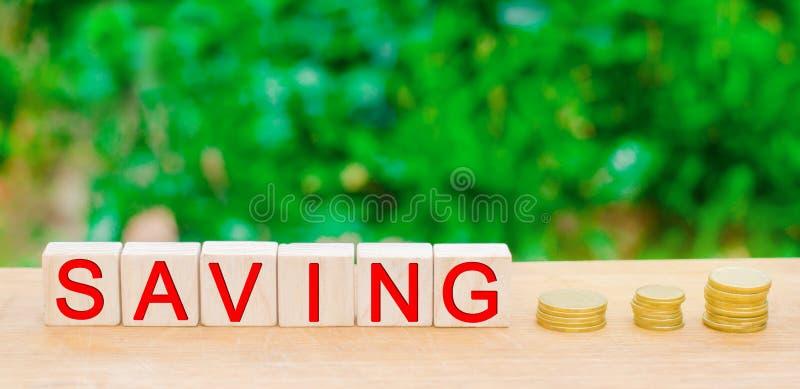 Blöcke mit dem Aufschrift ` Einsparung ` und Münzen Das Konzept der Investition in einem Geschäftsprojekt, der Grundstückserwerb, stockbilder