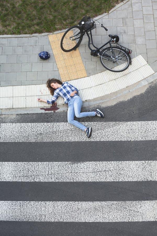 Blödande forcerat offer för bil bredvid cykeln royaltyfri foto