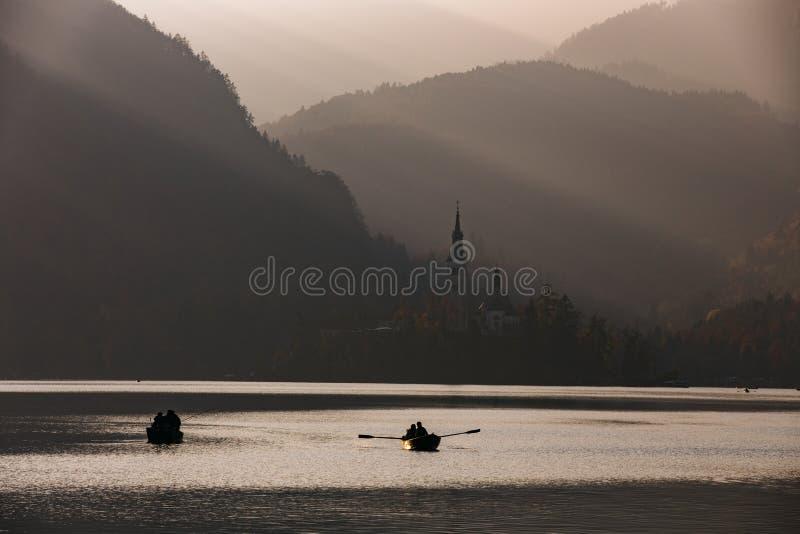 Blödd sjö i solnedgången med fartyget arkivbilder