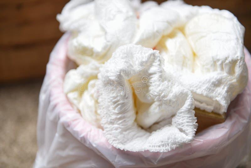 Blöjor slöser bort - smutsiga blöjor i en avskrädehink som kasserar av använt, behandla som ett barn nappies arkivbilder