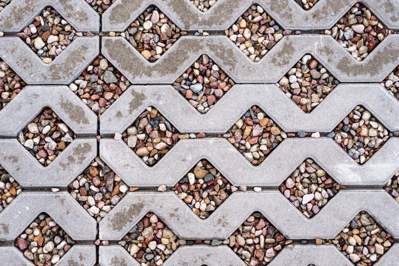 Blöta openwork konkret trottoar som fylls med färgrika kiselstenar royaltyfri foto