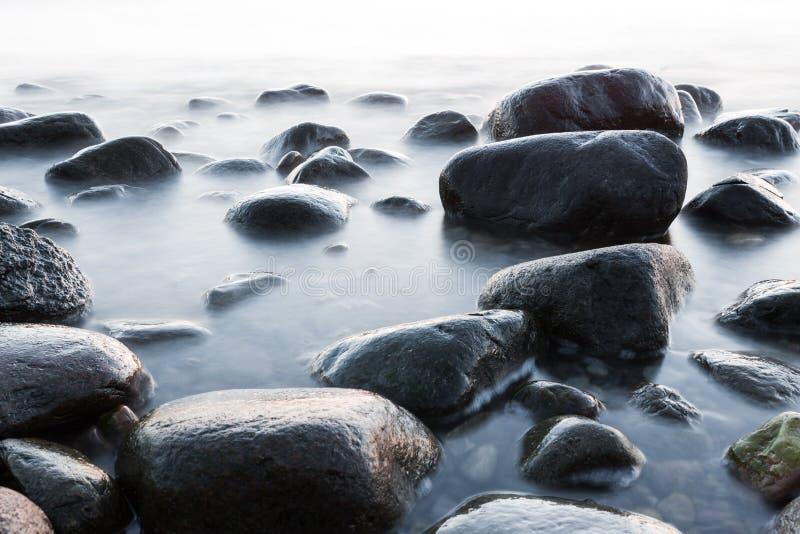 Blöta stenar vid havet fotografering för bildbyråer