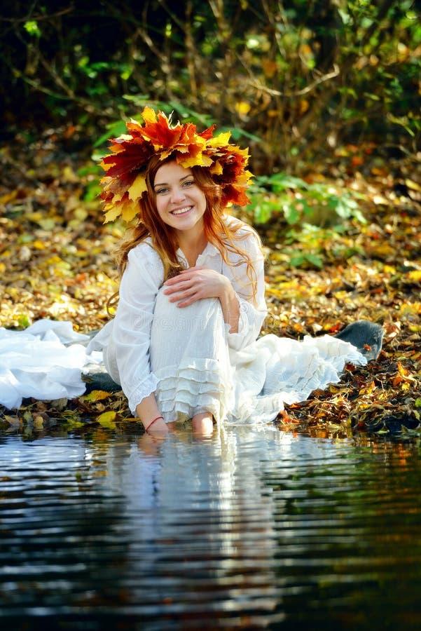 Blöter iklädd vit för den härliga flickan och att bära en krans av gula höstsidor och att sitta vid The Creek och fot i vatten på royaltyfri bild