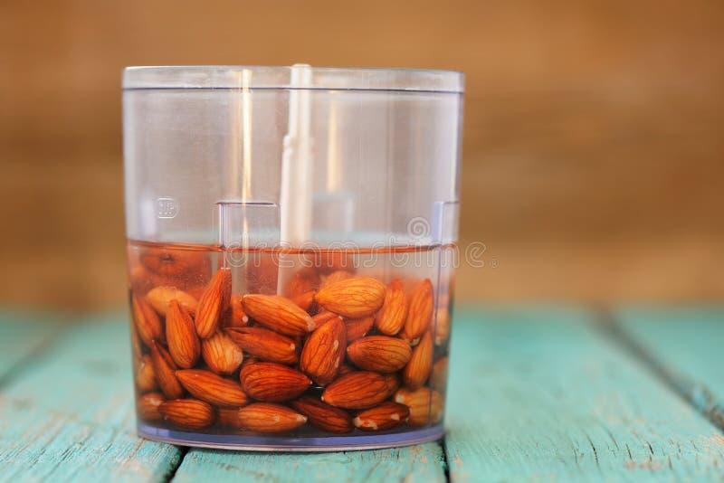 Blötta mandlar som är klara för framställning av mandeln, mjölkar i blandare royaltyfri foto