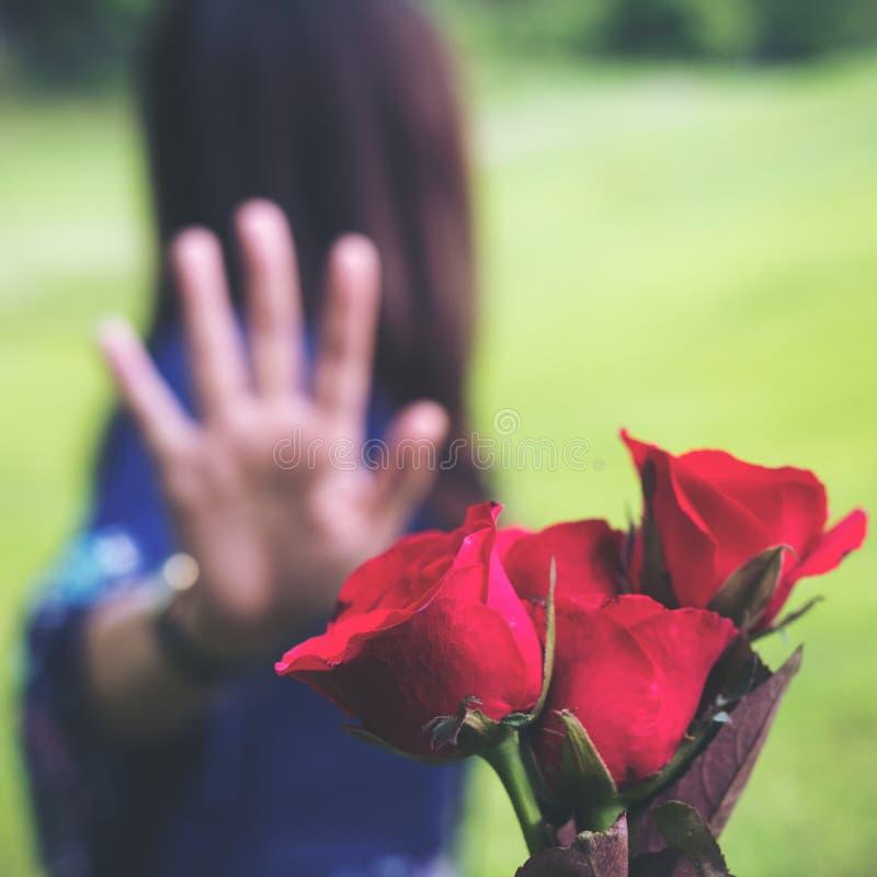 Blühen die Asiatinnen, die eine rote Rose zurückweisen, von ihrem Freund an Valentinsgruß ` s Tag mit Natur lizenzfreie stockbilder