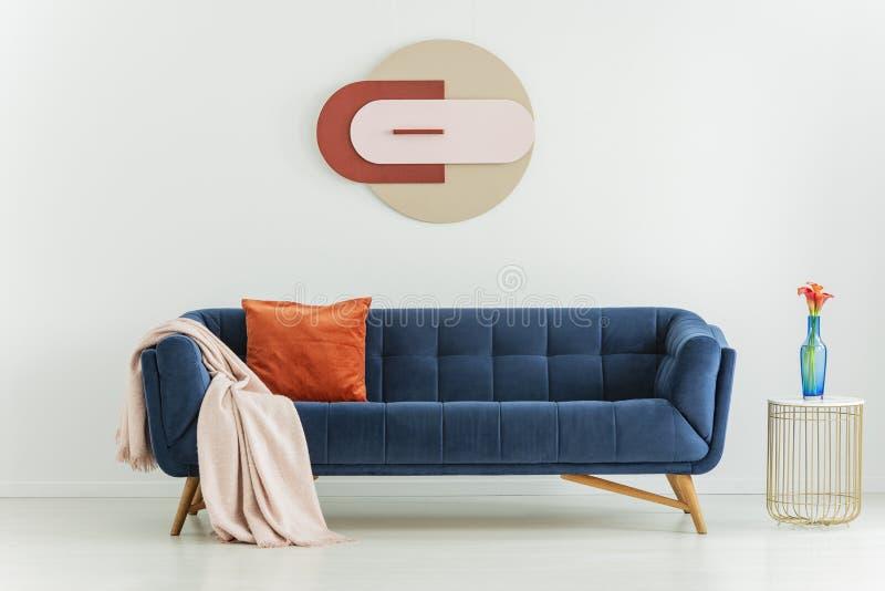 Blühen Sie auf Tabelle nahe bei blauer Couch mit orange Kissen und Decke im Innenraum mit Plakat Reales Foto stockfoto