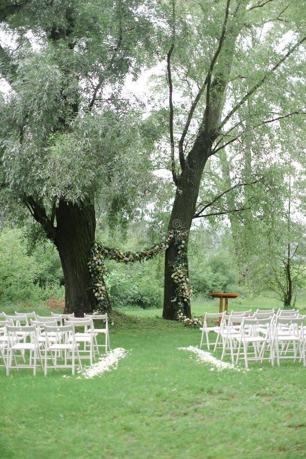 Blühen Sie Bogen für die Heiratsund weißen Stühle im Park lizenzfreie stockbilder