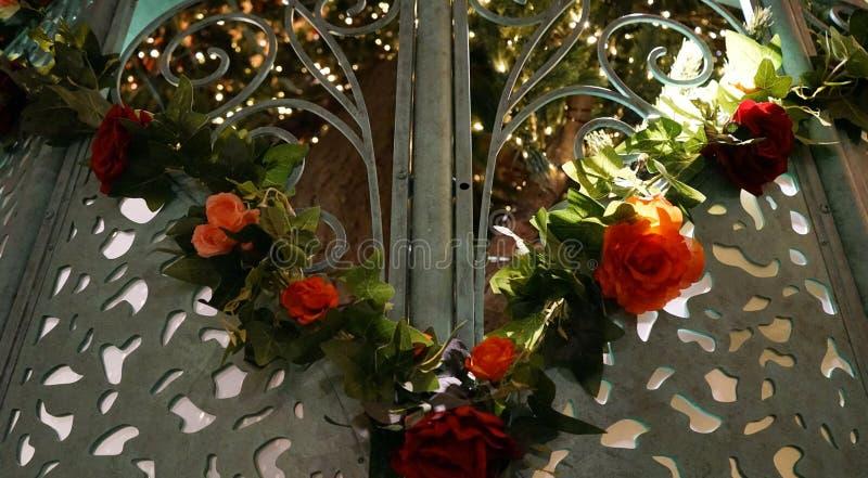 Blühen Sie Girlande auf den Toren, die in sonnenbeschienen Garten spähen stockfotografie