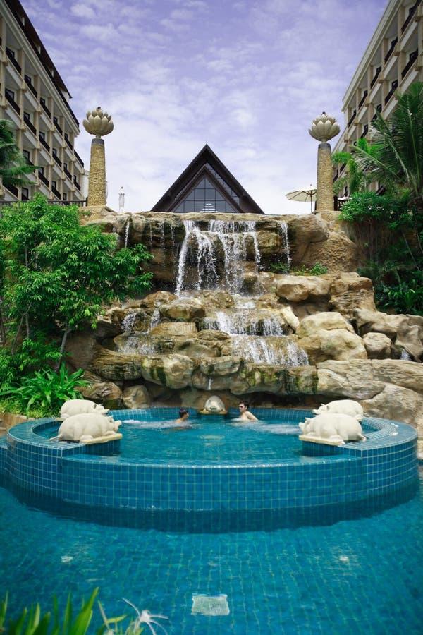 Blühen Sie Spalte, Wasserfall am Swimmingpool, Sonnenruhesessel nahe bei dem Garten und Gebäude stockbild