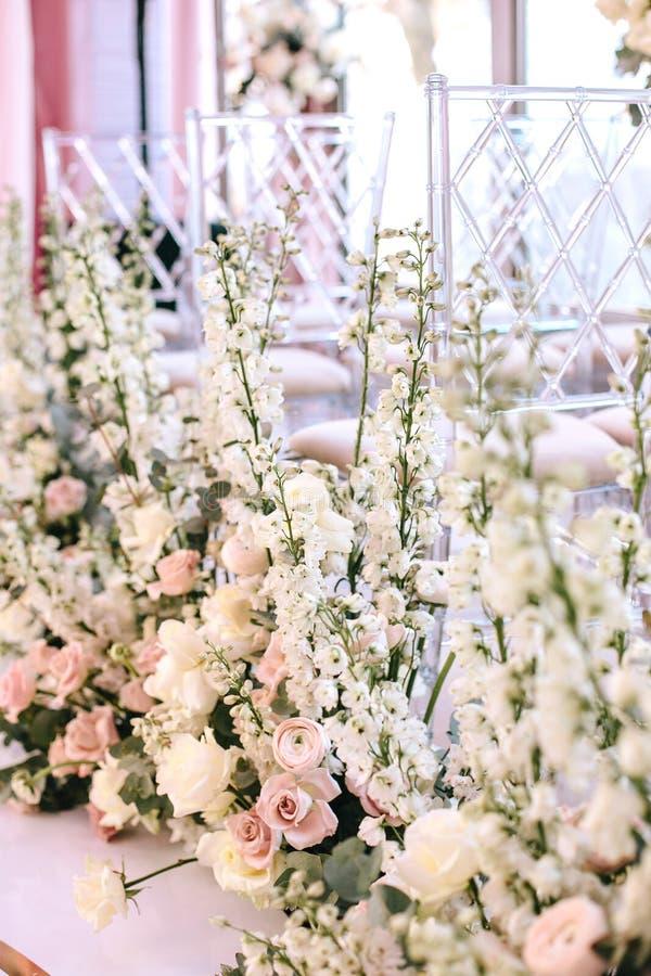 Blühen Sie Zusammensetzungen von Rosen, von Butterblumeen und von weißen Glocken nahe transparenten Stühlen an der Hochzeitszerem stockbilder