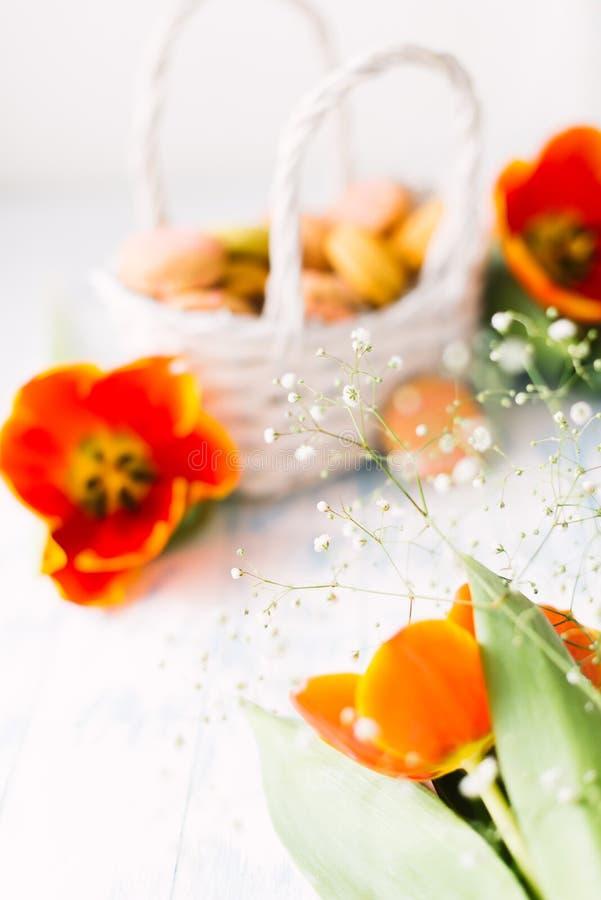 Blühende Tulpen mit Makronen auf einem hellen hölzernen Hintergrund Stillleben, Frühlingskonzept lizenzfreie stockbilder