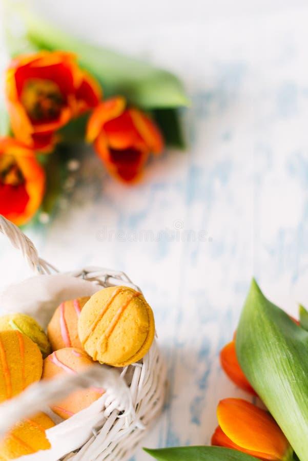 Blühende Tulpen mit Makronen auf einem hellen hölzernen Hintergrund Stillleben, Frühlingskonzept stockfotografie