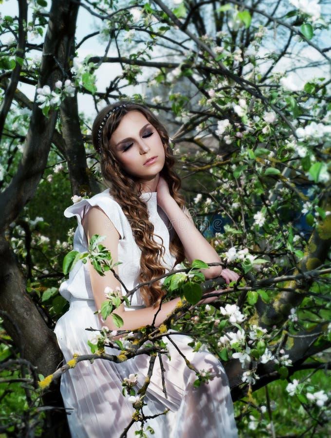 Blühender Garten. Hübsches Brautmädchensitzen stockbild
