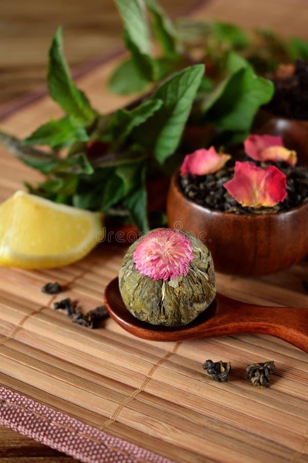 Blütenteeball und Blatttee mit den rosafarbenen Blumenblättern stockfoto