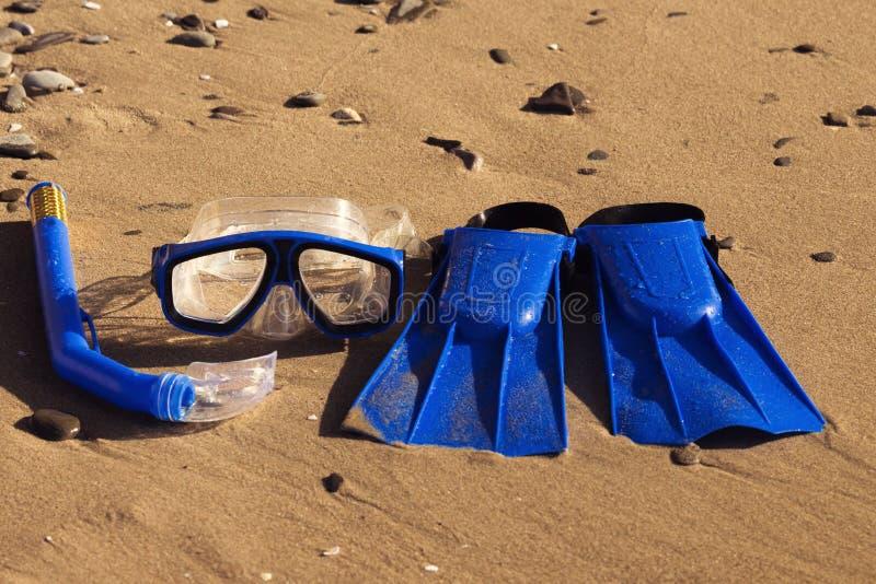 Bl?a badflipper, maskering, snorkel f?r br?nning som laing p? den sandiga stranden skal f?r hav f?r hav f?r bakgrundsstrandbegrep arkivfoton