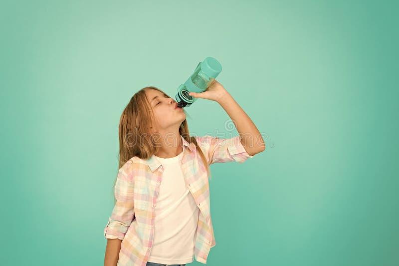 Bl? bakgrund f?r ungeh?llflaska Begrepp f?r vattenj?mvikt Sunt och hydratiserat Pediatriska oordningar av vattenj?mvikt flicka royaltyfria foton