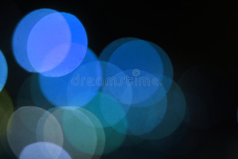 Bl?a defocused ljus p? svart bakgrund royaltyfria foton