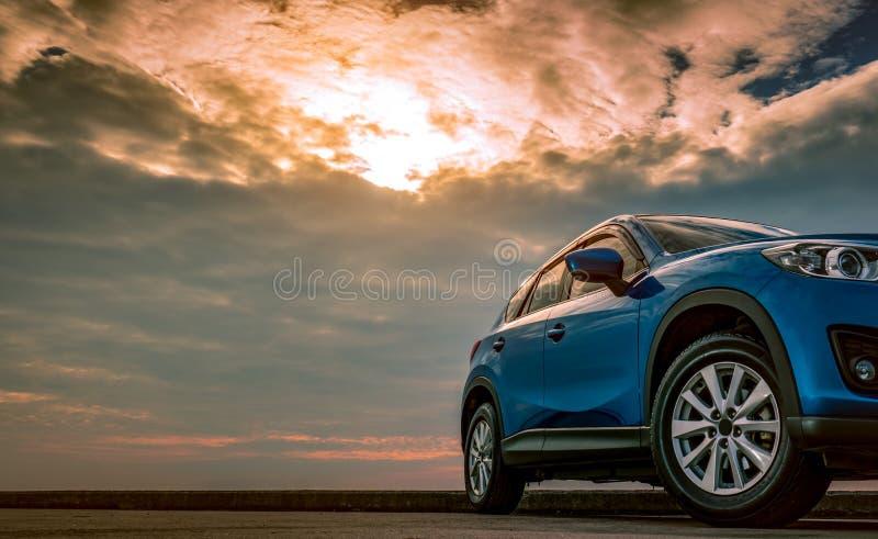 Bl? kompakt SUV bil med sporten och den moderna designen som parkeras p? den konkreta v?gen av havet p? solnedg?ngen i aftonen Hy royaltyfri fotografi