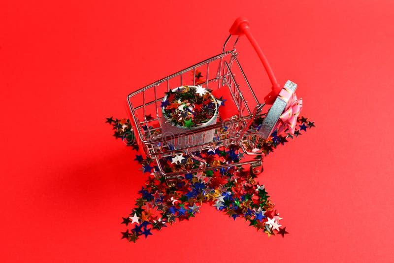 Bl? n?rvarande ask med den rosa pilb?gen i en shoppa vagn och konfettier p? en r?d bakgrund royaltyfri fotografi