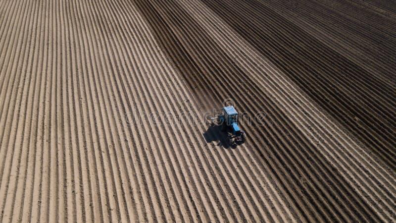 Bl? traktor som plogar f?ltet Flygfotografering med surret royaltyfri fotografi
