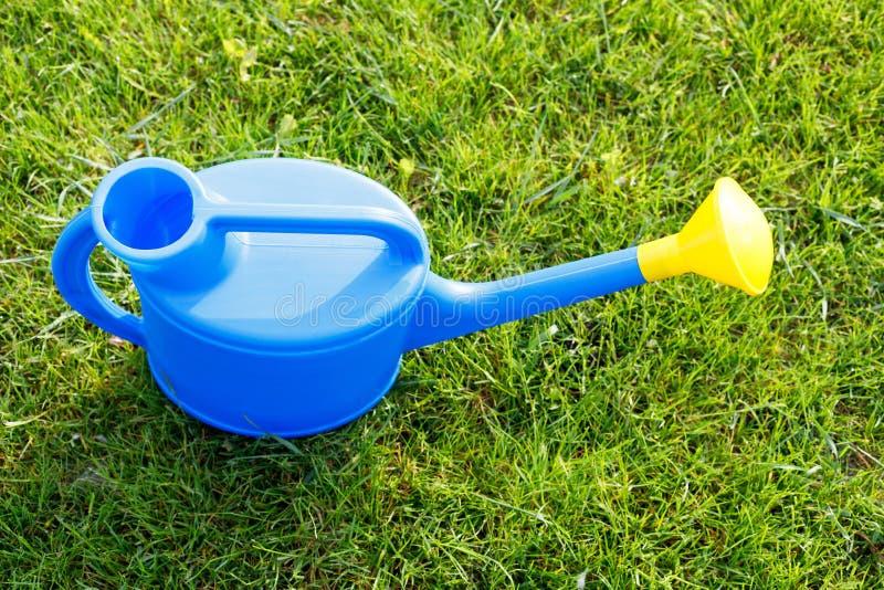Bl?tt plast- bevattna kan med en gul lins p? en gr?n gr?smatta p? en solig morgon royaltyfri fotografi