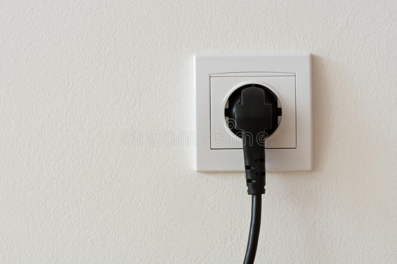 Black 220 volt power plug plugged in a socket. Close up photo of a black 220 volt power plug plugged in a socket with copyspace royalty free stock photo