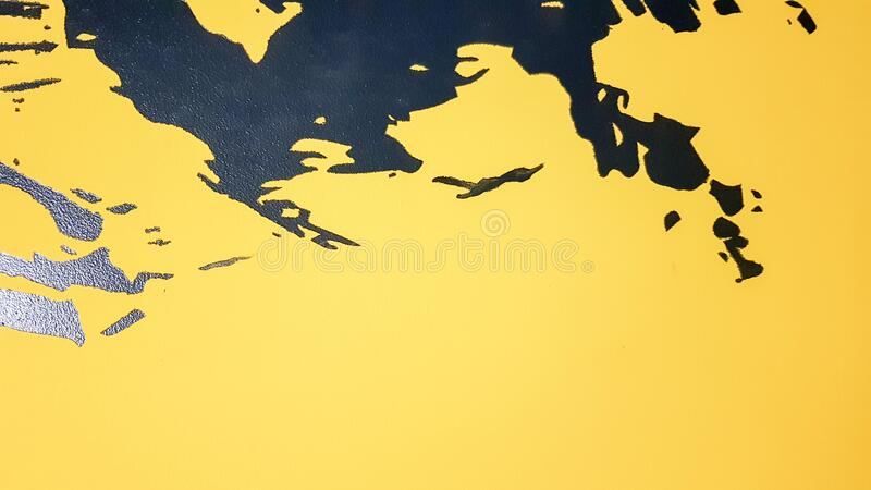 Black abstract paint splashes dripping on a bright yellow background. Black paint splashes on a yellow background. concept of art. Ideas. Paint brush texture royalty free stock images