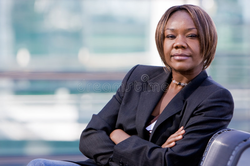 Black african american business woman. Posing in front of a modern office building with arms folded royalty free stock photo