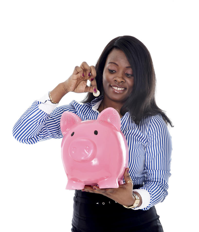 Black African American business woman putting coin into oversized pink piggybank stock photo