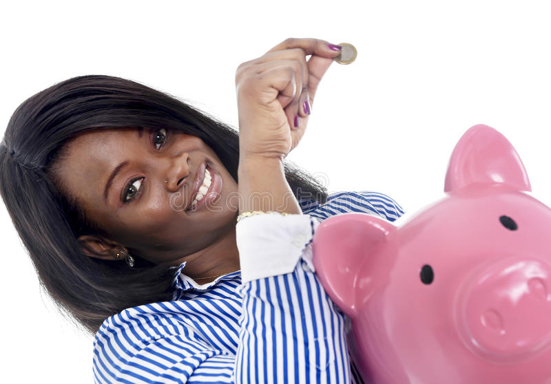 Black African American business woman putting coin into oversized pink piggybank. Young attractive black African American business woman putting coin into huge stock photography