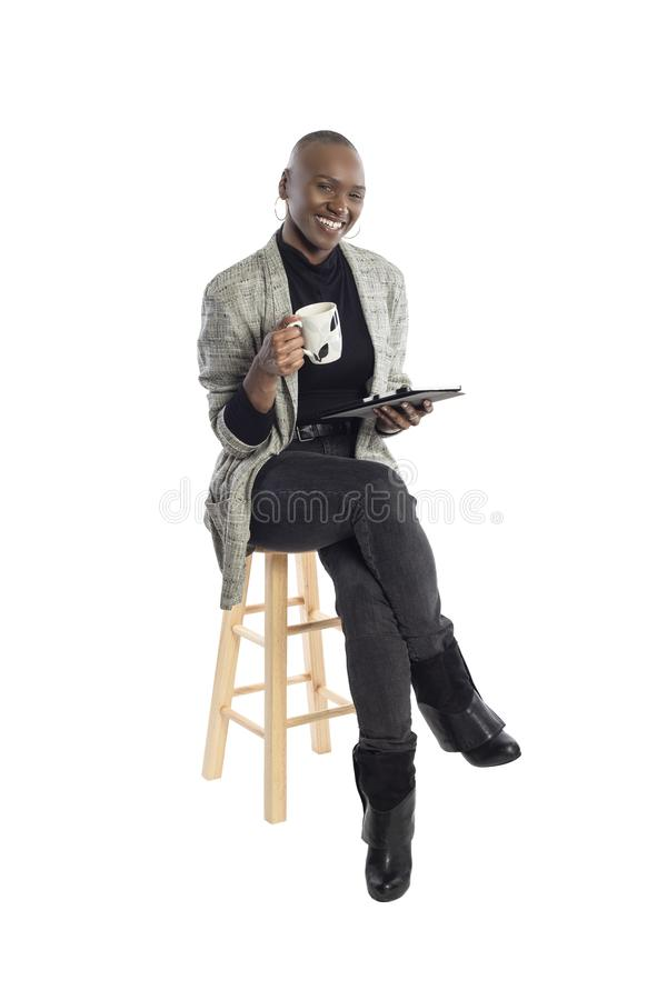 Black Female Author or Writer Posing with a Tablet and Coffee. Black African American businesswoman or writer as a keynote speaker for a seminar preparing for royalty free stock photo