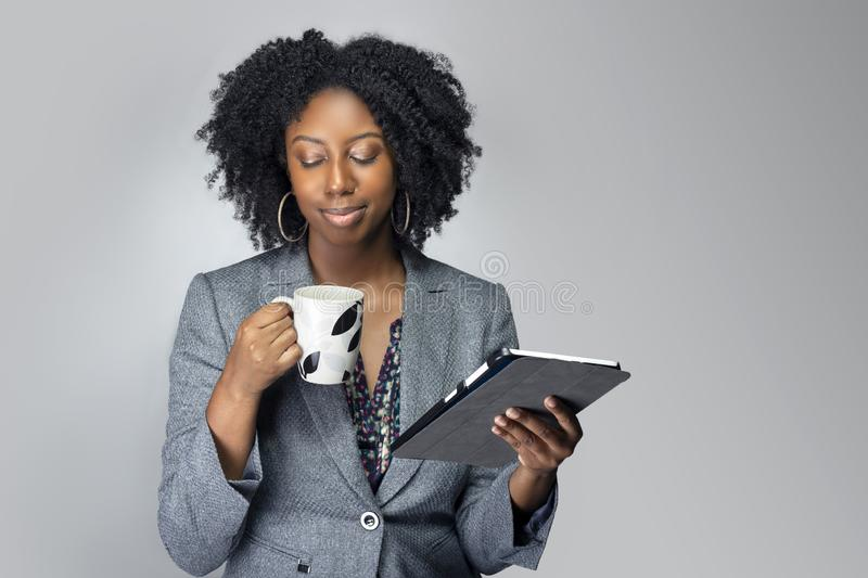 Black Female Businesswoman Keynote Speaker Posing with a Tablet and Coffee. Black African American businesswoman or writer as a keynote speaker for a seminar stock photos