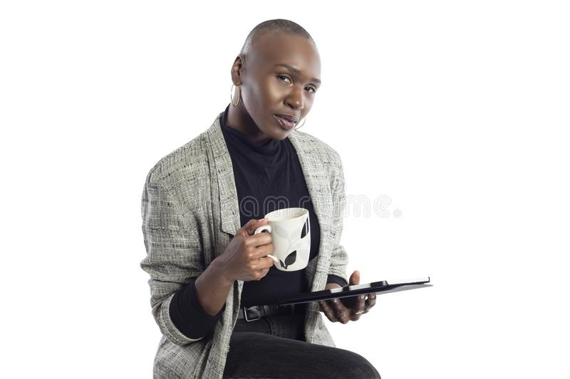 Black Female Author or Writer Posing with a Tablet and Coffee. Black African American businesswoman or writer as a keynote speaker for a seminar preparing for royalty free stock images