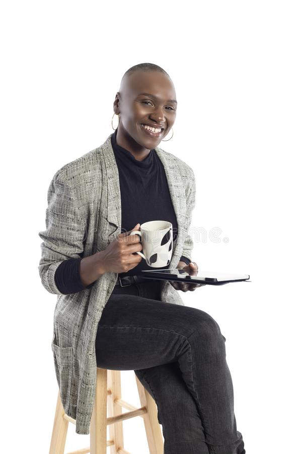 Black Female Author or Writer Posing with a Tablet and Coffee. Black African American businesswoman or writer as a keynote speaker for a seminar preparing for royalty free stock photography