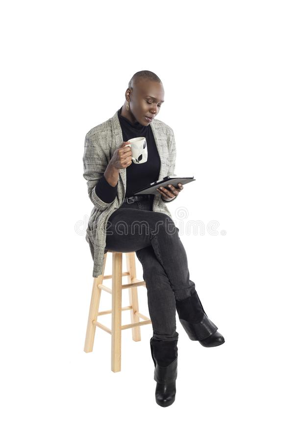 Black Female Author or Writer Posing with a Tablet and Coffee. Black African American businesswoman or writer as a keynote speaker for a seminar preparing for royalty free stock image