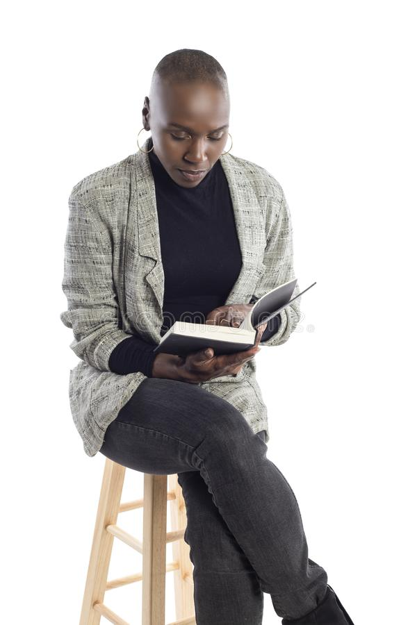Black Female Author or Writer Posing with a Book. Black African American female author sitting with a book like she is about to be a keynote speaker on a seminar royalty free stock photography