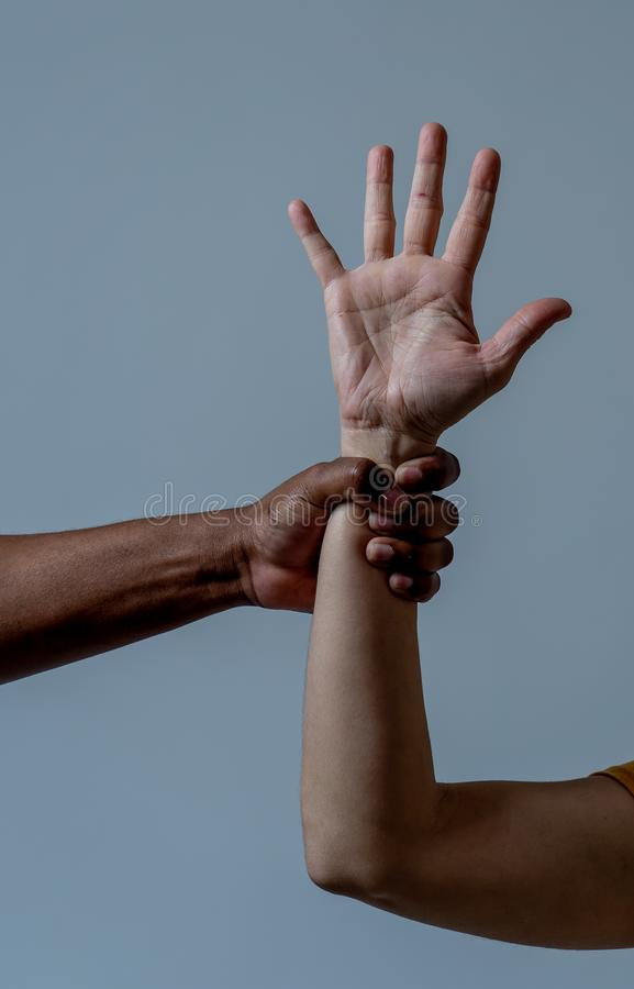 Conceptual image of humanitarian campaign to help refugees and multicultural cooperation. Black African American hand holding white skin arm. Conceptual image of stock photography