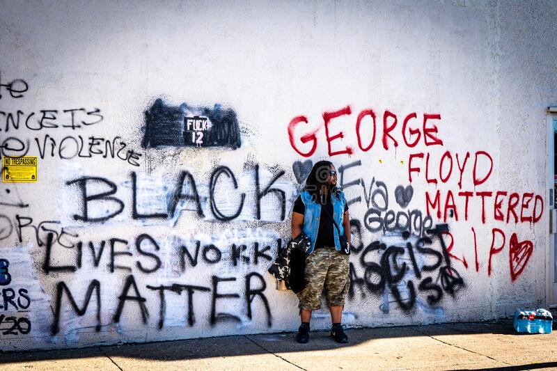 Black african american man standing in protest of george floyd police brutality. Minneapolis, Minnesota / USA - May 29, 2020: black african american man smoking stock images