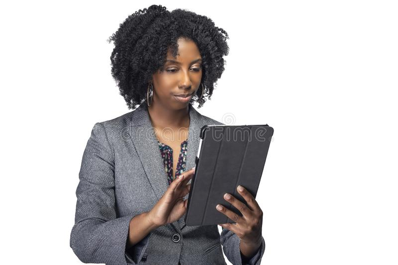 Female Author or Businesswoman Keynote Speaker with Tablet. Black African American teacher or businesswoman sitting and holding a tablet computer.  The confident royalty free stock image