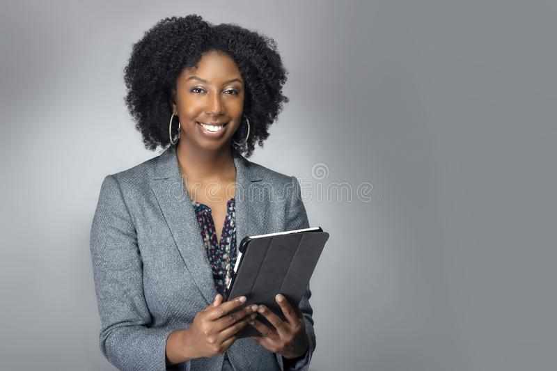 Female Author or Businesswoman Keynote Speaker with Tablet. Black African American teacher or businesswoman sitting and holding a tablet computer.  The confident stock photo