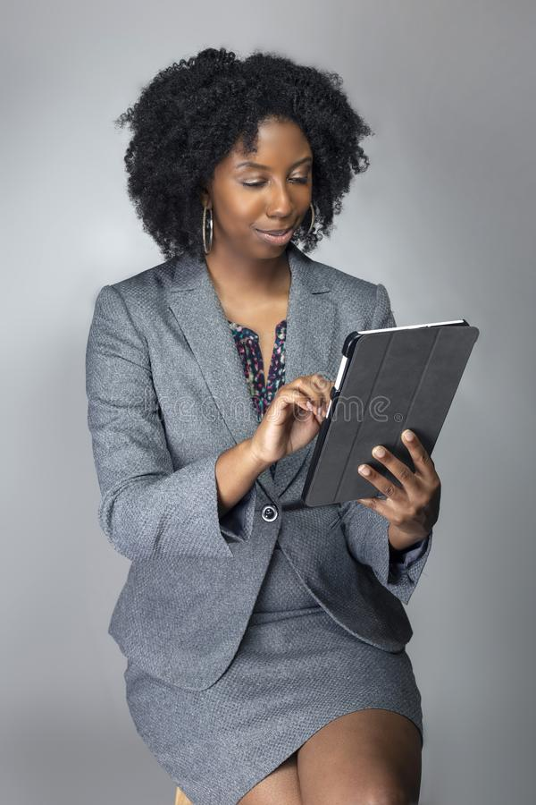 Female Author or Businesswoman Keynote Speaker with Tablet. Black African American teacher or businesswoman sitting and holding a tablet computer.  The confident stock photos