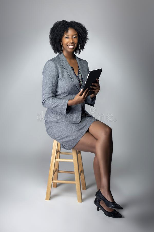Female Author or Businesswoman Keynote Speaker with Tablet. Black African American teacher or businesswoman sitting and holding a tablet computer.  The confident royalty free stock images