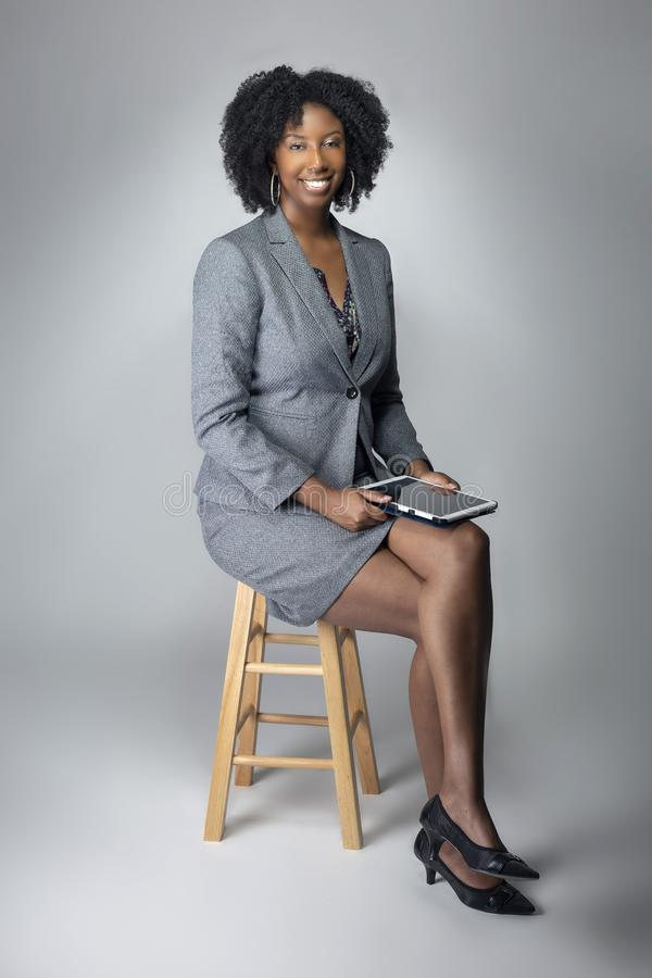 Female Author or Businesswoman Keynote Speaker with Tablet. Black African American teacher or businesswoman sitting and holding a tablet computer.  The confident royalty free stock photos
