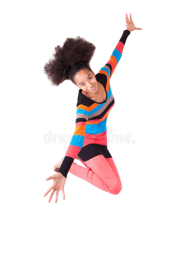 Black African American teenage girl with a afro haircut jumping. Of joy, isolated on white background stock photography