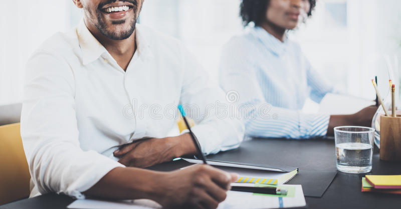 Black african businessman smiling in meeting room.Two young entrepreneurs working together in a modern office.Horizontal royalty free stock photography