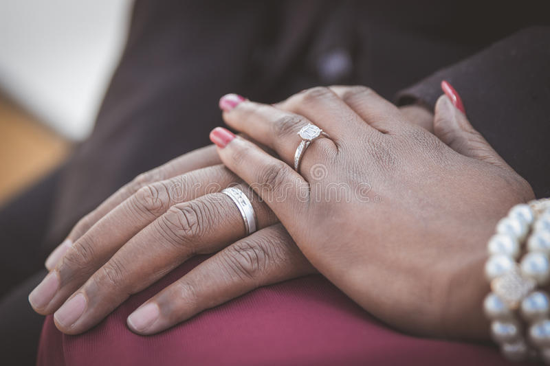 Black African couple sitting and holding hands royalty free stock photos