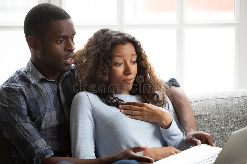 Black couple watching horror movie sitting on couch royalty free stock images